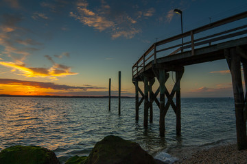 Large stones, a wooden pier, and a colorful sunset sky with clouds. West Neck Beach in Huntington, NY, USA.