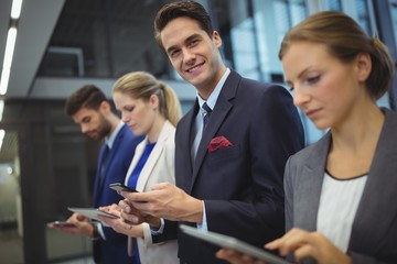 Business executives using electronic devices in corridor