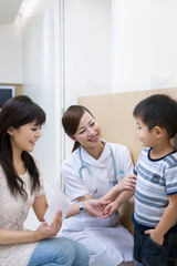 Female nurse talking to boy with mother at corridor