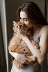 Vertical image of pretty woman in nightie kissing cat