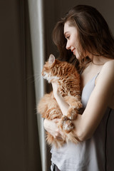 Vertical image of pleased woman in nightie holding cat