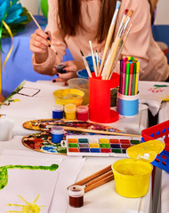 Kindergarten tables with painting brush and teacher in interior decoration . Preschool class waiting kids. Playroom with white table. Art room for education children's creativity.