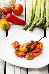 Roasted bell peppers with tomato sauce on the white rectangular plate. Rustic style.