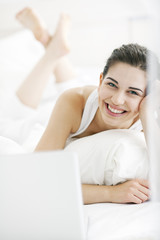 Beautiful young woman using a laptop in bed