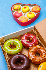 Glazed donuts and macaroons. Sweet dessert in delivery box. Almond macaron cookies. On wooden table.