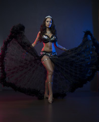Sexy slim woman, belly dancer in black costume with crystals. Dark background with pink and blue lightening