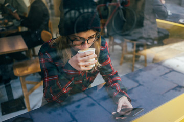 Young woman drinks coffee and works from phone wearing flannel shirt and beanie photo through window