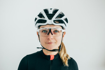 Professional cyclist portrait in front of white wall in white helmet and black jersey wearing clear lens glasses
