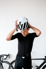 Professional cyclist preparing for a bike ride all white room all black outfit putting on helmet with bikes in back