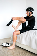 Professional cyclist preparing on bed for a bike ride all white room all black outfit putting on socks and shoes