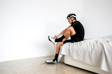 Professional cyclist preparing on bed for a bike ride all white room all black outfit putting on shoes