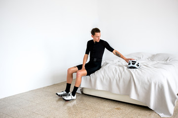 Professional cyclist preparing on bed for a bike ride all white room all black outfit reaching for white helmet