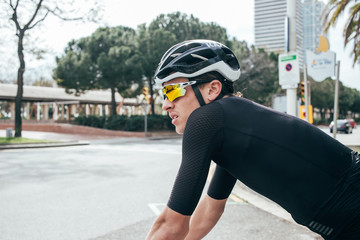 Professional cyclist in all black waits at traffic light with yellow lens glasses and city in background