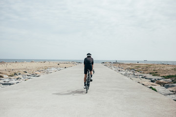 Professional cyclist in all black riding off into the distance toward sea as ride comes to an end beach and rocks