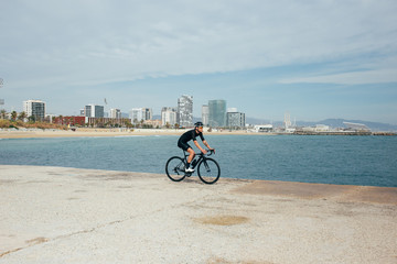 Professional cyclist in all black riding along the seaside overlooking cityscape and beach in nice light
