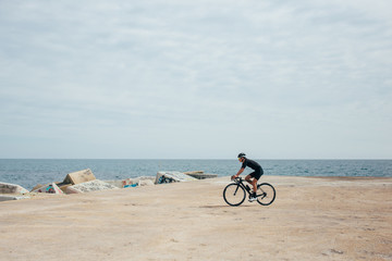 Male professional cyclist rides around a pier wearing all black near blue sea and rocky port nice light.
