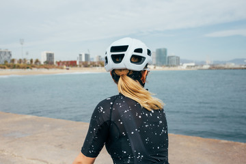 Female blonde cyclist stares at cityscape from pier near sea