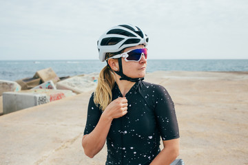 Female cyclist in black with white helmet and glasses zips jersey on pier near sea