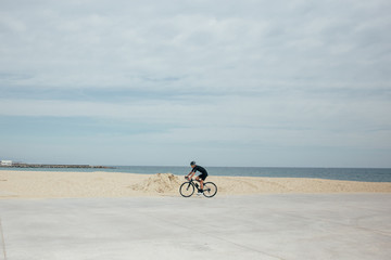 Professional cyclist in black on pier near the sea with orange lenses on bicycle next to sand