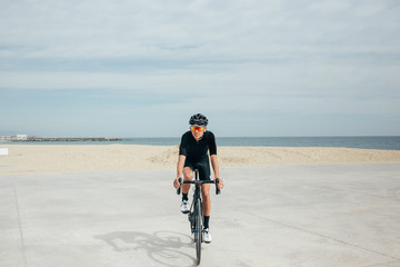 Professional cyclist in black looking at camera on pier near the sea with orange lenses on bicycle with shadow