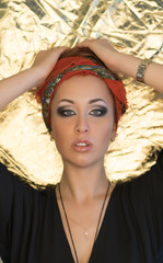 Makeup. Beautiful woman, elegant lady, original style, gold background. Brunette with red headband