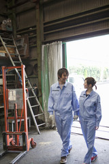 Male and Female Factory Workers Walking