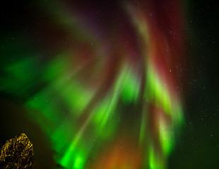 Aurora borealis (Polar lights) over Lilandstinden peak and Hamnoy village in the North of Europe - Reine, Lofoten islands, Norway