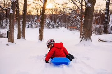 Rear view of boy riding a toboggan down a snow slope