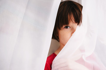 Girl hiding behind a curtain