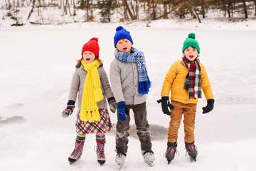 Three children on ice skates singing carols
