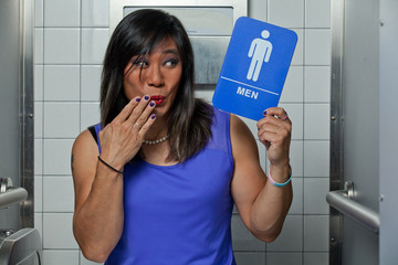 Transgender female in bathroom stall with surprised worried face looking at men's restroom sign.
