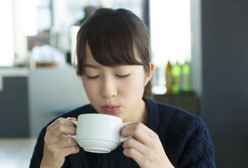 若い女性 カフェで寛ぐ 熱いスープ カフェオレを口で冷ますイメージ
