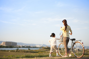 Girl with mother walking at riverbank, mother pushing bicycle, copy space