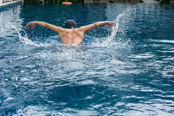 Asia Man doing butterfly strokes while swimming with splash of water pool. View of back Male swimmer performing the butterfly stroke at outdoor swimming pool. Asian Thailand.