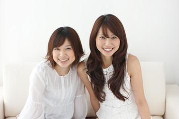 Portrait of two young women sitting on sofa, smiling