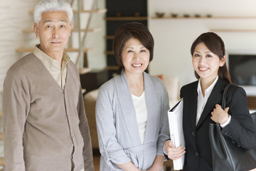 Portrait of young businesswoman and senior couple in living room, smiling