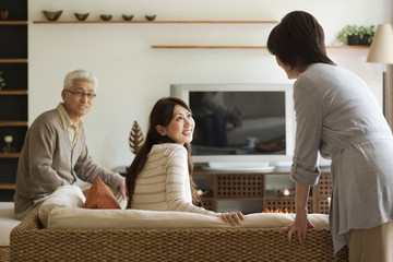 Family in living room, mother talking to daughter on sofa