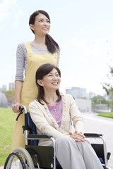 Caretaker pushing mature woman on wheelchair