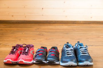 Sneakers for the whole family for sports on the wooden floor