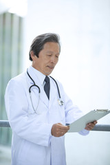 Male doctor with clipboard standing outdoors
