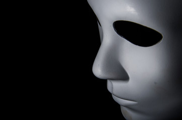White mask with neutral expression and shadows on dark background