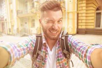 Tourist man making selfie photo smile. Bearded man in plaid shirt with backpack smiling for the camera outdoors in the city street. Toned image.