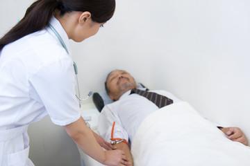 Female nurse preparing saline drip for mature man