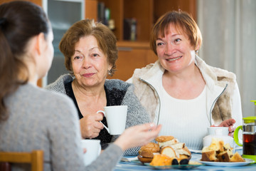 Senior women talking with girl while tea drinking