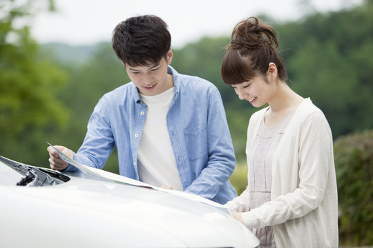 Couple looking at a map in front of a car