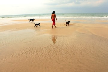Asian man with three black dogs enjoy walking on the beach
