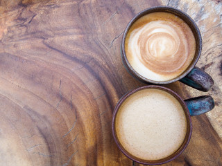Two cups of hot coffee cappuccino on wood texture background, top view.