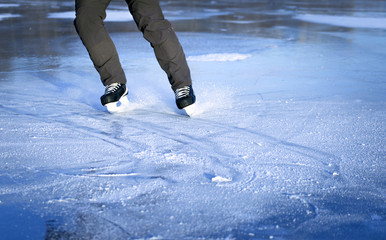 The guy rides on skates on ice in the winter.