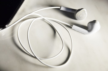 Black Mobile phone and white headphones.