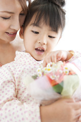 Girl with mother holding flower bouquet, white background